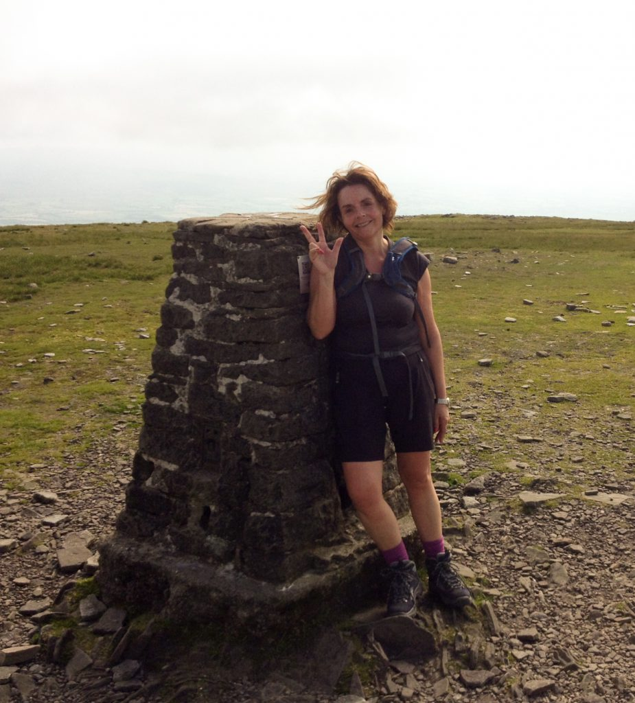 Woman standing at the top of a mountain